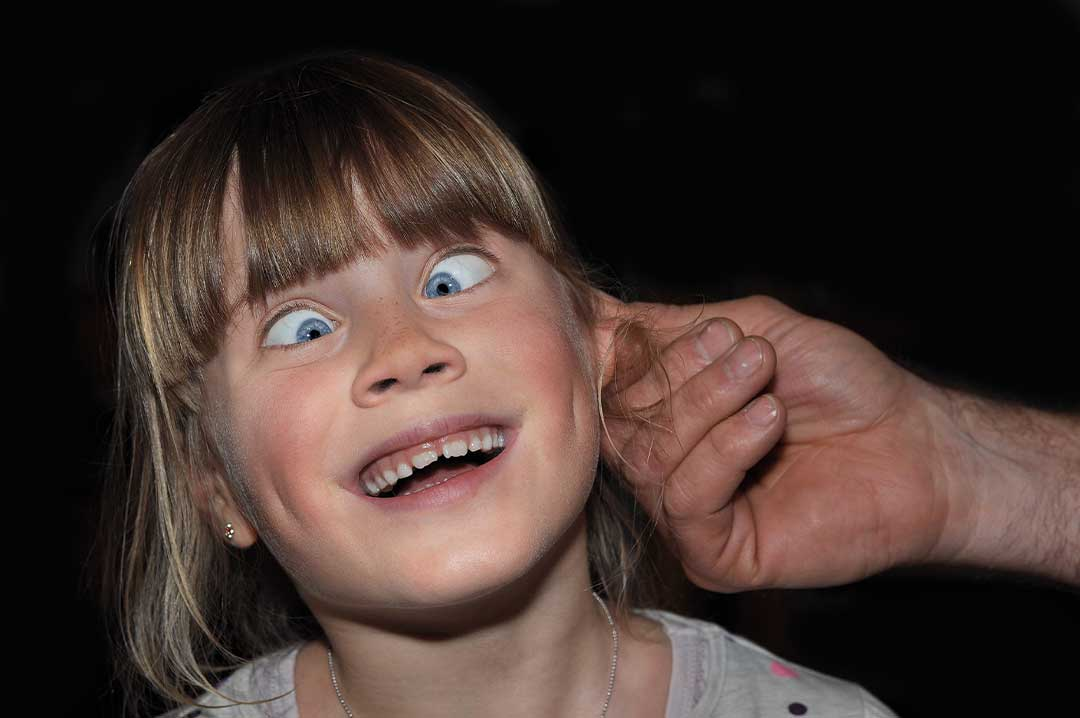 Child playfully having her ear pulled