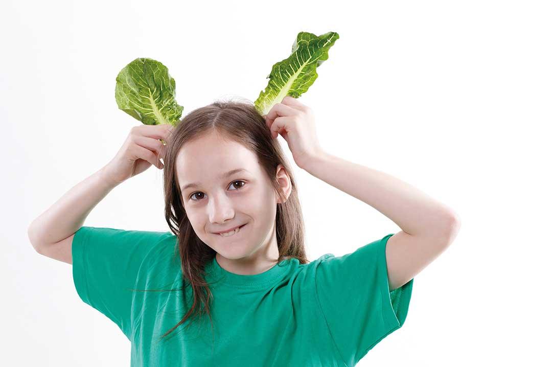 Girl joking with lettuce as ears