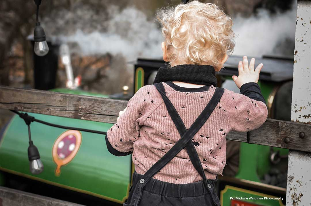 Child looking at a steam train